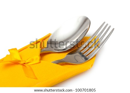 Fork and spoon in a yellow cloth with a bow isolated on white - stock photo