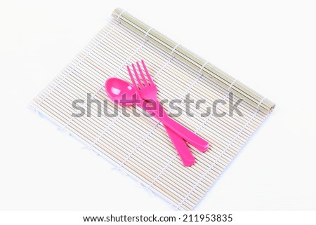 Fork and spoon on bamboo mat  - stock photo
