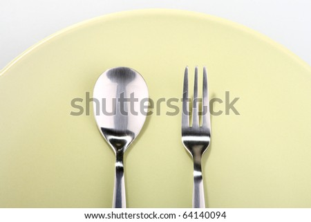 fork and spoon on green plate - stock photo