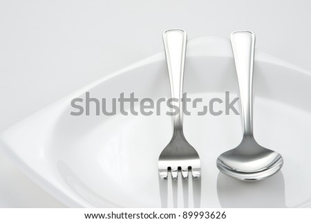 Fork and Spoon on white dish - stock photo