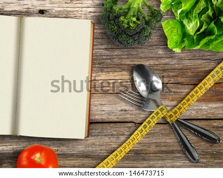 Fork and spoon tied with tape measure with book and vegetables on wooden background (diet concept) - stock photo