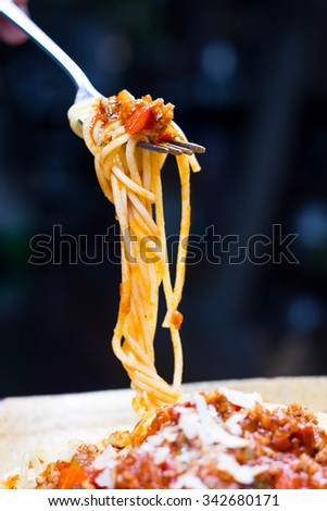 Fork full of twirled Italian spaghetti with a Bolognese meat sauce and basil suspended in the air above a full plate of food against a grey background - stock photo