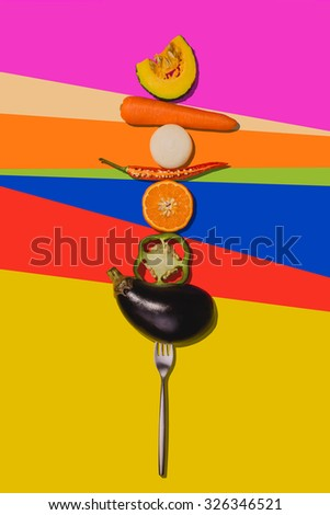 Fork impale vegetables on colorful background. - stock photo