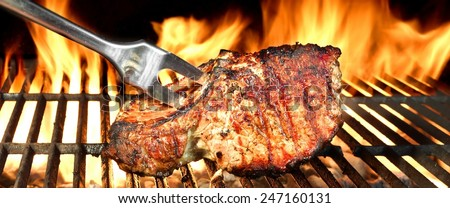 Fork in Grilled Pork Chop on  BBQ Grill, Flames of Fire on the Black Background. - stock photo