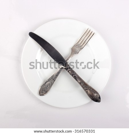 Fork, knife and dinner plate isolated on white  - stock photo