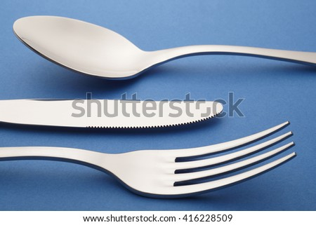 Fork knife spoon detail over a blue textured background. Cutlery. Vertical - stock photo