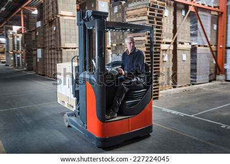 Fork lift operator drives through warehouse and is preparing the products for shipment - stock photo