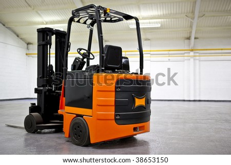 Fork Lift Truck in empty Warehouse - stock photo