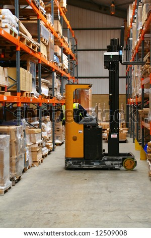Fork Lift Truck in Warehouse with forklift driver - stock photo