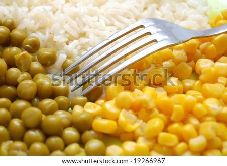 Fork on dish of rice, green peas and sweet corn