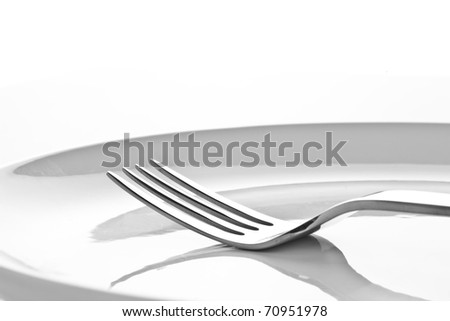fork on white plate - stock photo