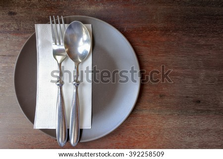Fork plate spoon isolated on wooden table