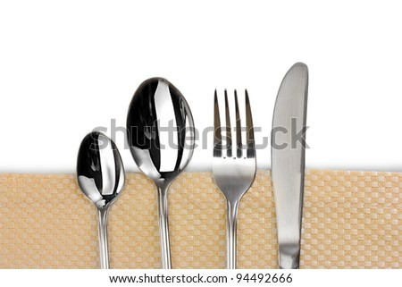 Fork, spoon and knife on a beige tablecloth