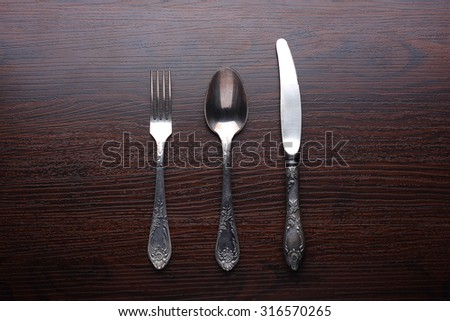 Fork, spoon and knife on wooden table - stock photo