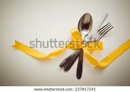 Fork, spoon and knife with decorative ribbon. - stock photo