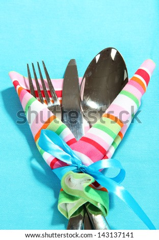 Fork,spoon,knife in napkin on bright background - stock photo