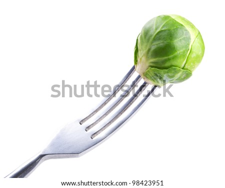 fork with fresh green Brussels sprouts over white - stock photo