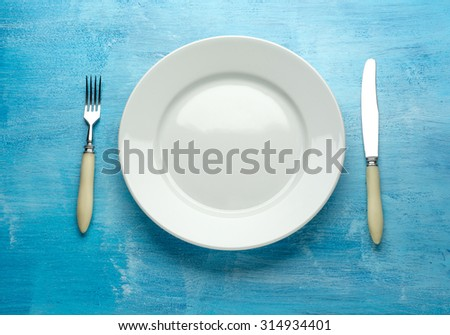 Fork with knife and blank plates. On wooden table background - stock photo
