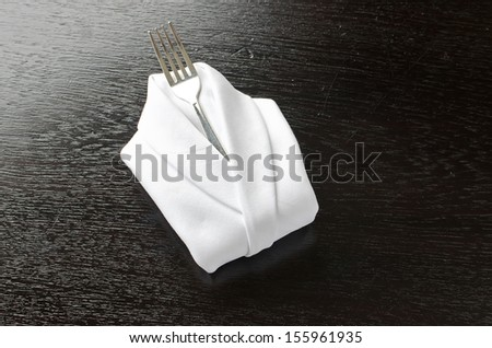 Fork with Linen serviette Folded like  Shirt on the Wooden table background