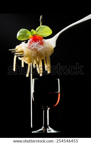 fork with macaroni and glass of red wine on black background - stock photo