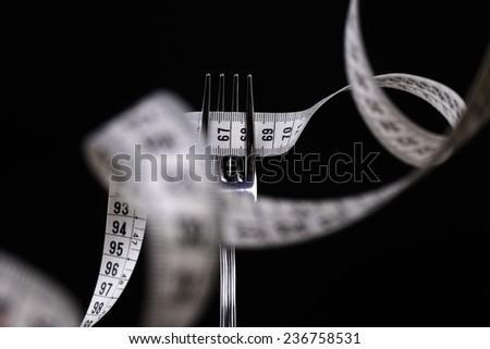 Fork with measure tape - stock photo