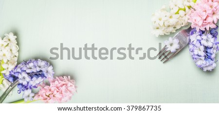 Fork with spring hyacinth  flowers on light green shabby  rustic background, top view, banner. Festive table place setting and cooking. - stock photo