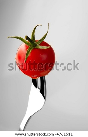 fork with tomato - stock photo