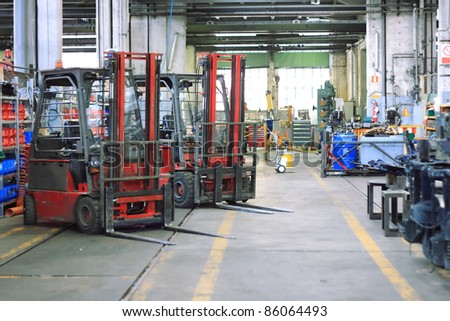 forklift and tools in machine shop - stock photo