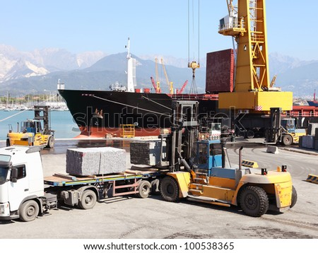 forklift and truck  in harbor loading cargo ship - stock photo