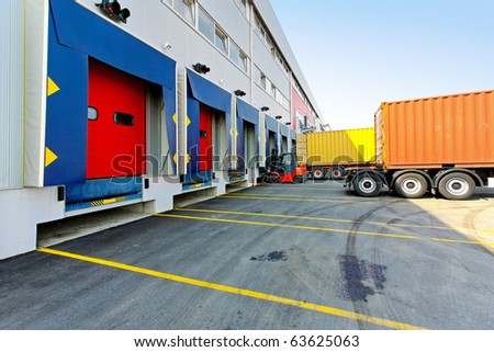 Forklift and trucks at cargo dock of warehouse - stock photo
