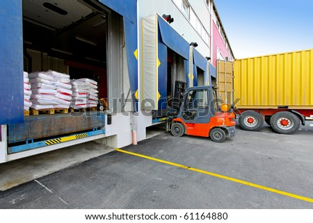 Forklift at cargo dock of big warehouse - stock photo