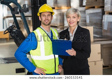 Forklift driver and his manager smiling at camera in a large warehouse - stock photo