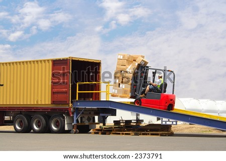 Forklift driver loading truck - stock photo