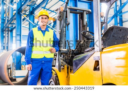 Forklift driver standing proud in manufacturing plant - stock photo