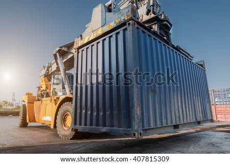 forklift handling container box loading from dock to truck - stock photo