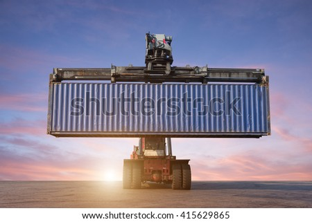 Forklift handling container box loading in the port at Thailand at sunset - stock photo