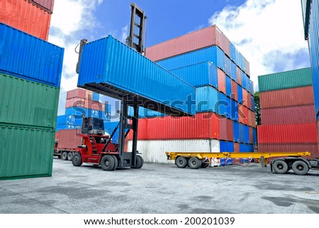 forklift handling container box loading to truck in dock - stock photo