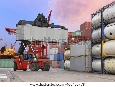 forklift handling the container box at dockyard with harbour background