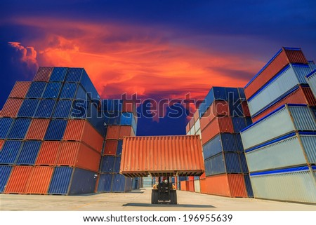 Forklift handling the container box in sunset - stock photo