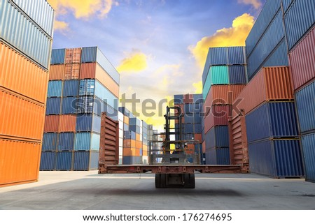 forklift handling the flat rack container box at dockyard with beautiful sky - stock photo