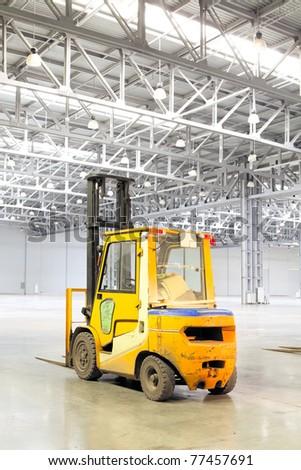 Forklift loader in large modern storehouse - stock photo