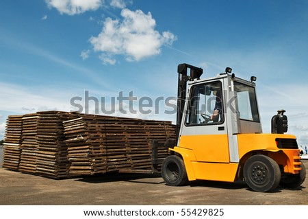 Forklift loader making warehouse works outdoors by stacking wood pallet