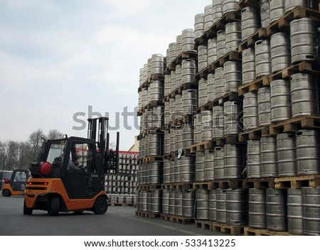 Forklift loading beer kegs in warehouse brewery