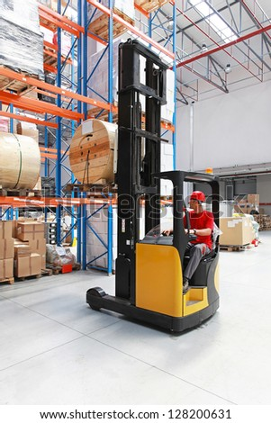 Forklift loading pallet with roll in distribution warehouse - stock photo