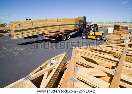 Forklift loading remade trusses onto a trailer - stock photo