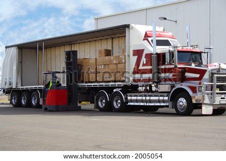 Forklift loading truck - stock photo