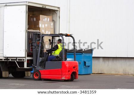 Forklift loading truck - stock photo