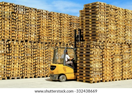 Forklift Operator Between Rows of Transport Pallets - stock photo