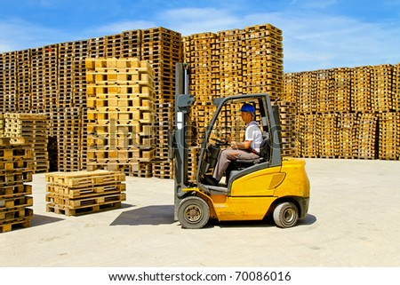 Forklift operator handling wooden pallets in warehouse - stock photo