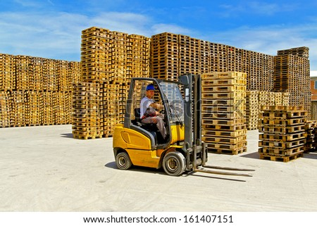 Forklift operator in pallet warehouse on the open  - stock photo